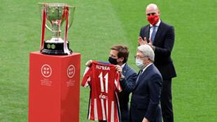 El alcalde de Madrid, José Luis Martínez Almeida (I) sostiene junto al trofeo de La Liga una camiseta del Atlético de Madrid junto al presidente del club flamante campeón español, Enrique Cerezo (C), y el presidente de la Real Federación Española de Fútbol (RFEF), Luis Rubiales (D), en el estadio Wanda Metropolitano de Madrid el 23 de mayo de 2021.