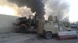 Des véhicules de l'armée irakienne en feu, à Mossoul, après la prise de la ville par EIIL.