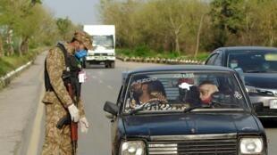 Un militaire contrôle une famille à bord d'un véhicule aux abords d'Islamabad, la capitale du Pakistan, le 25 mars 2020.