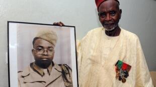 Le vétéran sénégalais Issa Cissé montre une photo de lui datant de 1944, année du débarquement de Provence.
