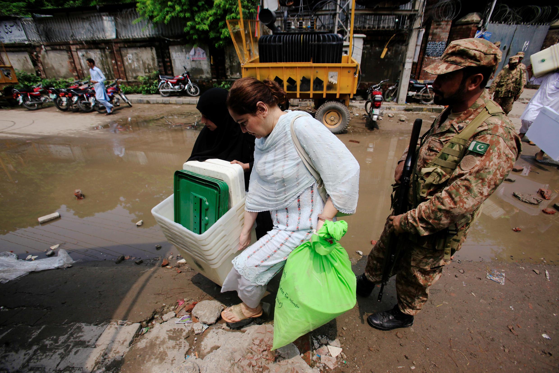 Lahore, Pakistan: une employée achemine le matériel électoral pour les élections législatives, sous la garde d'un soldat, le 24 juillet 2018.