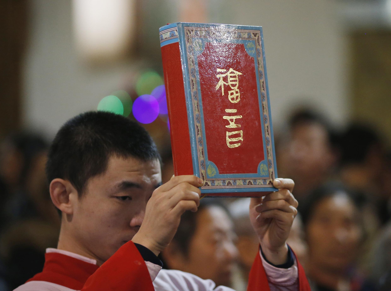 Một giáo dân Công giáo giơ cao kinh thánh trong một buổi lễ thánh tại Bắc Kinh ngày 24/01/2014.