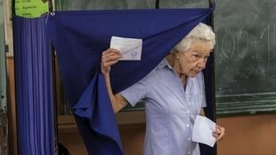 A Greek woman leaves the polling booth in Athens on Sunday 5 July