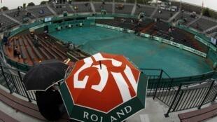 Espectadores bajo los paraguas esperando a que la lluvia cese en el Roland Garros, París 27 de mayo de 2010.