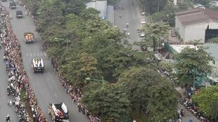 Mourners pay respects as Vietnamese soldiers transport the artillery cart carrying the coffin of General Vo Nguyen Giap