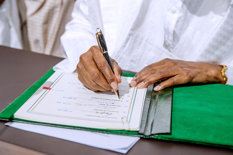 O presidente nigeriano Muhammadu Buhari assina um acordo antes do lançamento da Área de Livre Comércio Continental Africana (AfCFTA), durante a cimeira da União Africana em Niamey, Níger, 7 de Julho de 2019.
