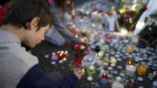 Jovens acendem velas em homenagem às vítimas dos atentados de novembro em Paris