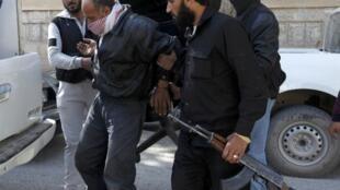 Члены исламистской группировки Джабхат ан-Нусра с захваченным заложником в Ракке 14/03/2013 (архив)