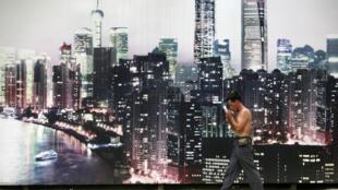 Chi phí cao khiến nhiều doanh nghiệp nước ngoài muốn rời Trung Quốc. Trong ảnh : một công nhân đi dạo cạnh một khu phố lớn của Thượng Hải, 13/07/2012