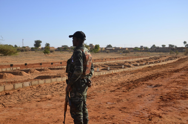 Soldado nigerino a olhar para as sepulturas de militares mortos num ataque jihadista a 10 de Dezembro de 2019. Níger.