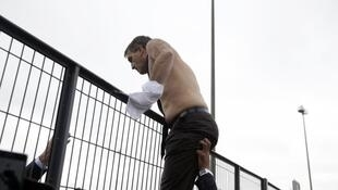 Air France's head of human resources, Xavier Broseta, tries to scale a fence shirtless, after hundreds of workers invaded the airline's headquarters on October 5, 2015.
