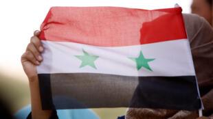 Una mujer muestra una bandera siria en Deraa, Siria, el pasado 4 de julio de 2018.