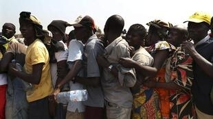 People stand in line for aid distribution near Bangui airport camp, 8 January 2014.