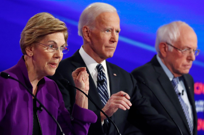 Elizabeth Warren (L), Joe Biden and Bernie Sanders at the Democratic debate in Iowa, 14 January 2020.