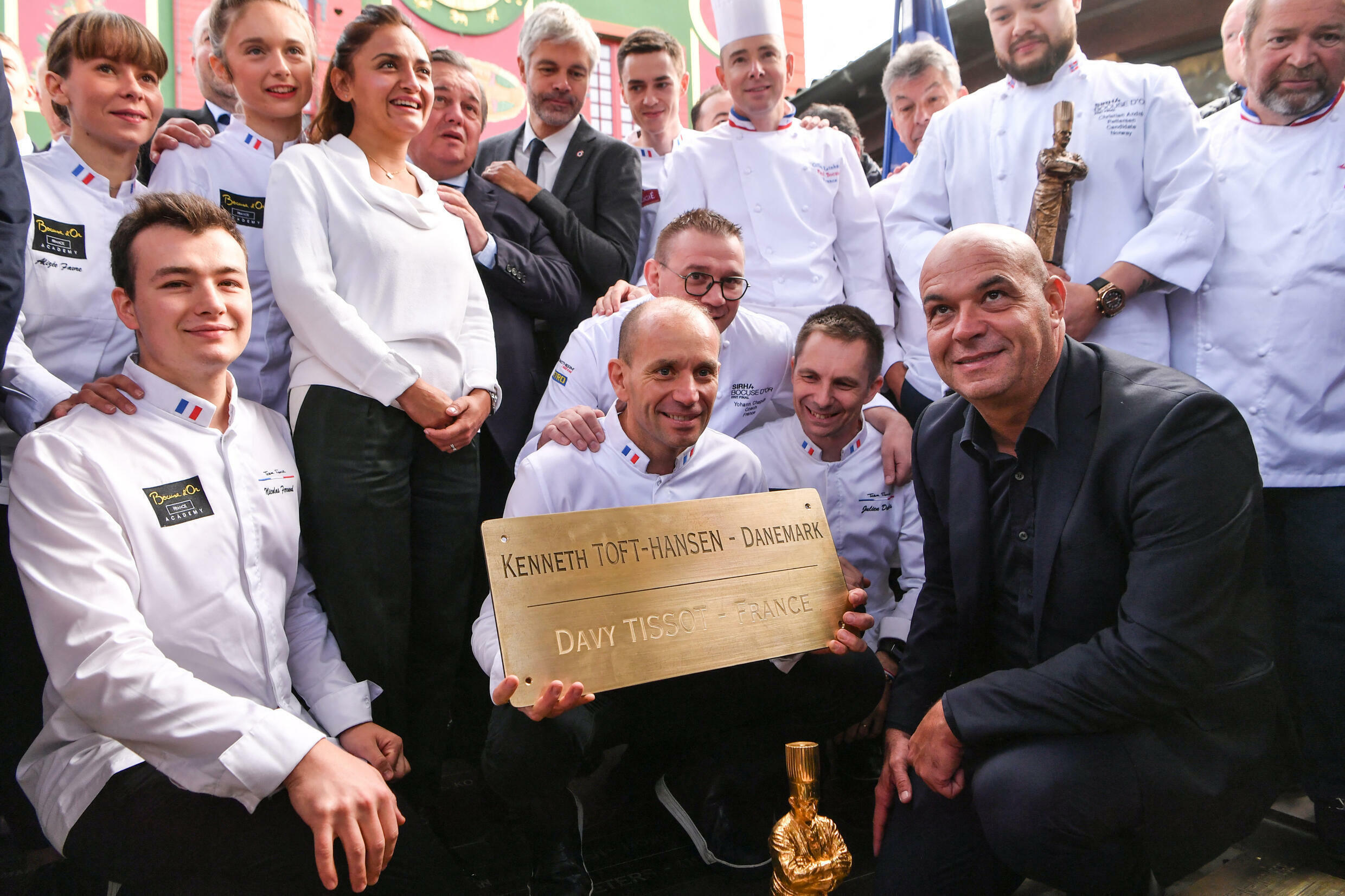 French chef Davy Tissot (C) holds a memorial plaque next to Jerome Bocuse (R down), son of famous French chef Paul Bocuse and members of his team, after winning the Bocuse d'Or 2021 international food award, in Collonges-au-Mont-d'Or on 28 September, 2021.