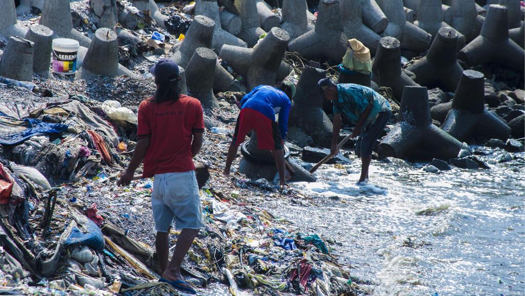 Des ouvriers indonésiens extraient du sable d'une plage polluée.
