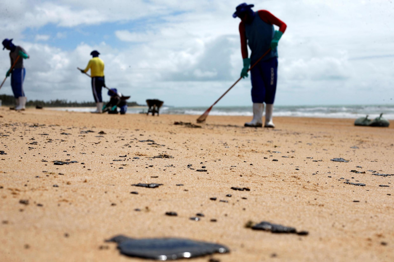 Profissionais retiram petróleo das areias da praia de Coruripe, no Alagoas, em 14 de outubro de 2019.