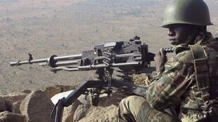 A Cameroonian soldier guards at an observation post on a hill in the Mandara Mountain chain in Mabass overlooking Nigeria, north