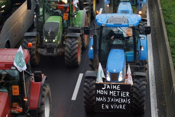 """French farmers drive their tractors on their way to Paris, 27 November 2019. The slogan reads """"I love my job, but I would like to live off of it."""""""