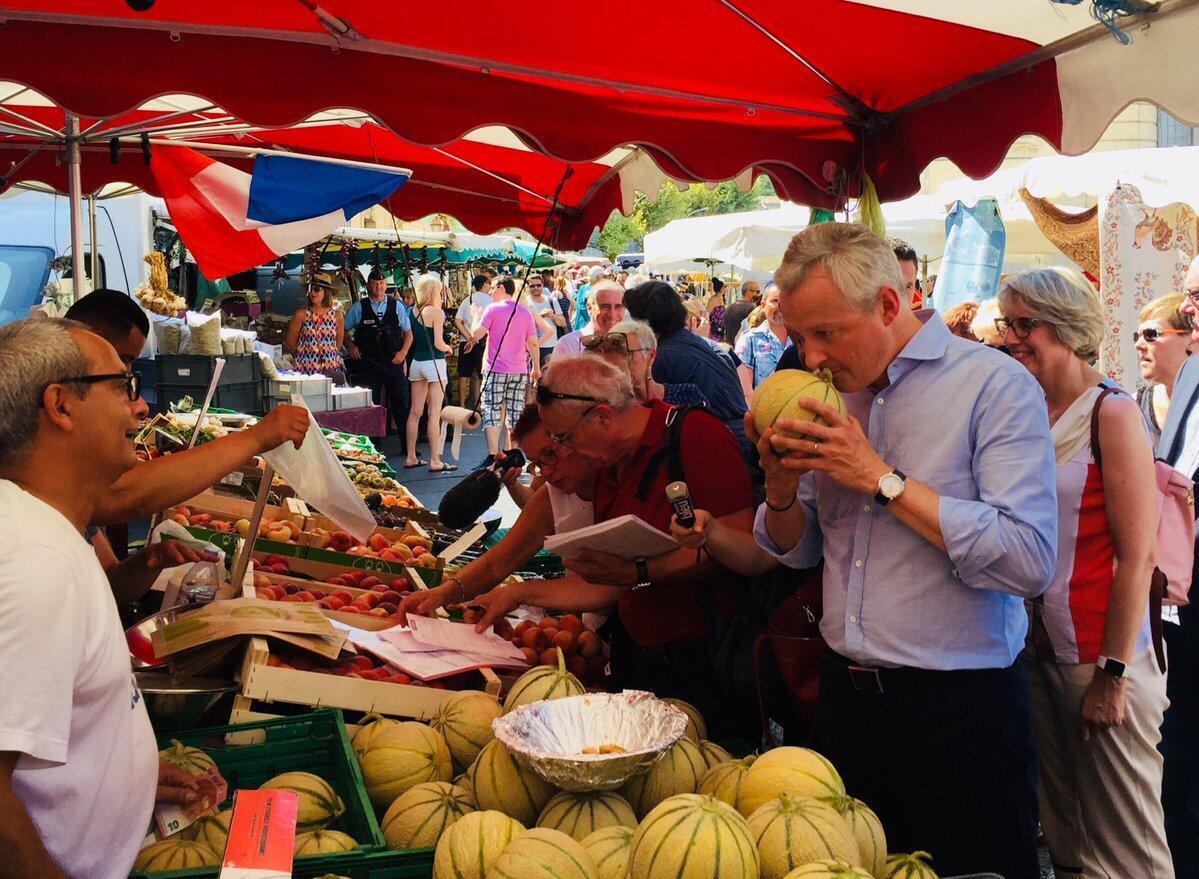 Министр экономики Брюно Ле Мер проверяет качество дынь на рынке в Апте