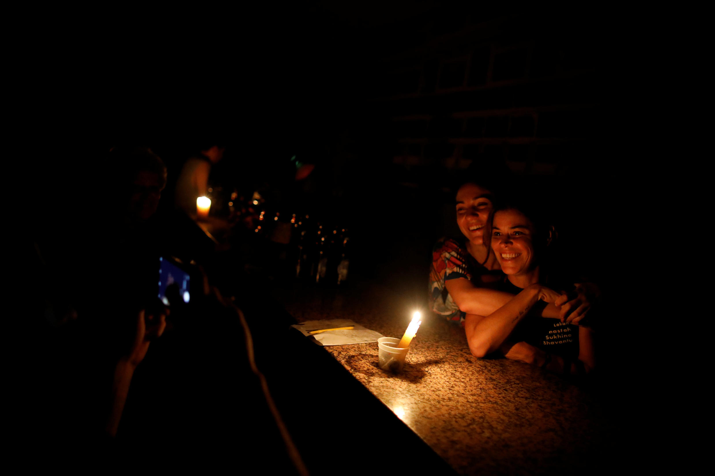 Pessoas, em um bar, posam para foto durante um blecaute em Caracas, Venezuela 29 de março de 2019.