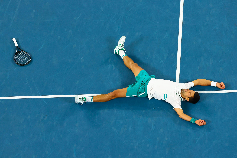 Novak Djokovic falls to ground in joy after beating Russia's Daniil Medvedev in the Australian Open men's singles final