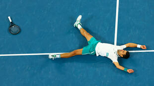 Novak Djokovic falls to ground in joy after beating Russia's Daniil Medvedev in the Australian Open men's singles final