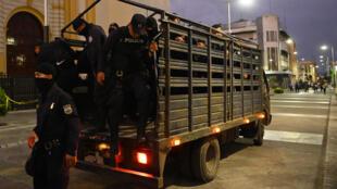 Un grupo de policías baja de un vehículo en una calle del centro histórico de San Salvador para aplicar la orden gubernamental de cuarentena domiciliaria para combatir el coronavirus, al anochecer del 21 de marzo de 2020 en la capital de El Salvador