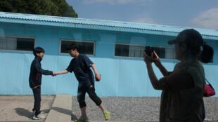 Une femme prend une photo de garçons imitant la poignée de main entre les dirigeants nord-coréen Kim Jong Un et sud-coréen Moon Jae-in dans un studio de cinéma reconstituant Panmunjom, à Namyangju en Corée du Sud 8 mai 2018.
