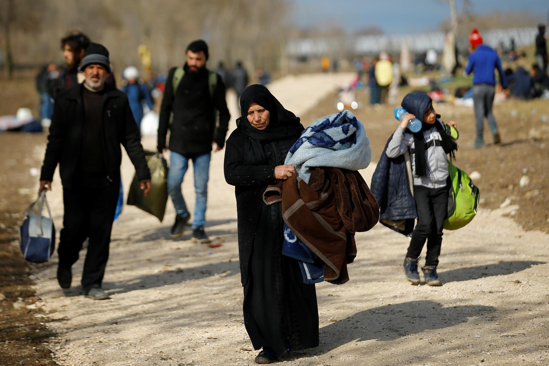 Les migrants marchent vers la frontière alors qu'ils se heurtent à la police anti-émeute grecque au poste-frontière turc de Pazarkule, près d'Edirne, le 6 mars 2020.