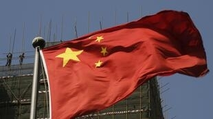 Labourers working at a construction site are pictured behind a Chinese flag in Beijing April 24, 2013.
