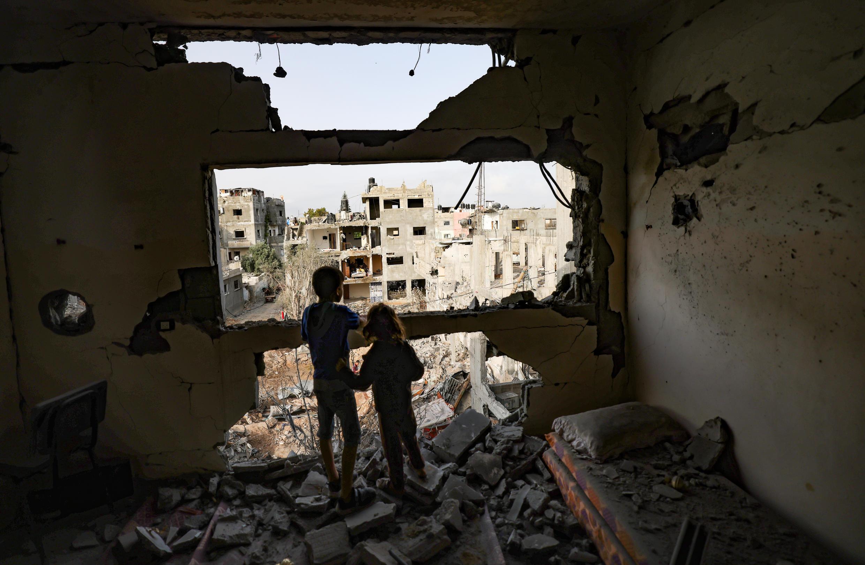 Dos niños miran las destrucciones causadas por los bombardeos israelíes en su barrio de Gaza,el 21 de mayo de 2021