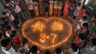 Students light candles and pray for the victims of the Zhouqu landslide, in Yuncheng
