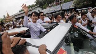 A líder democrática de Myanmar, Aung San Suu Kyi, acena para birmaneses em Yangon, nesta segunda-feira.