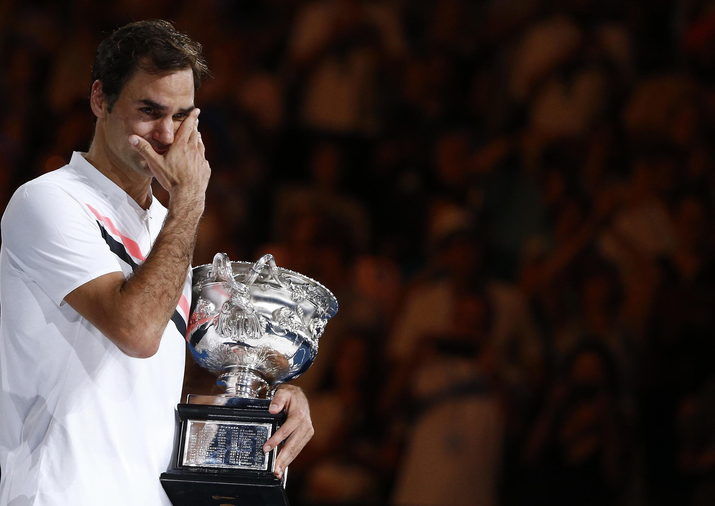 Roger Federer of Switzerland cries as he holds the trophy after winning the Australian Open.
