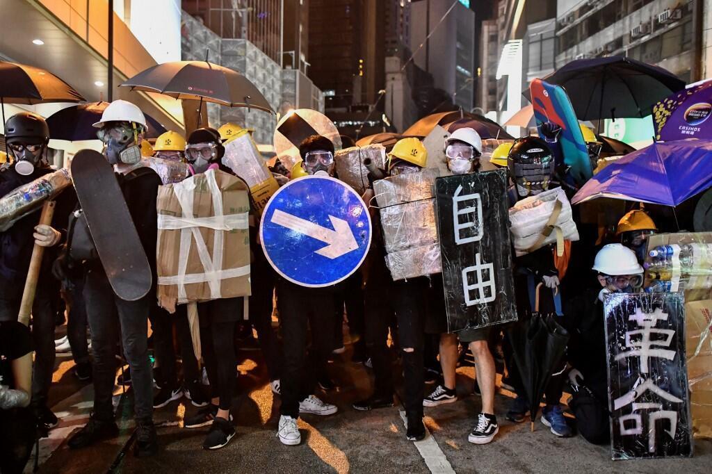 Manifestantes em Hong Kong se protegem com escudos feitos por placas de sinalização urbanas, cartazes com mensagens, e até skates,em 28 de julho de 2019.