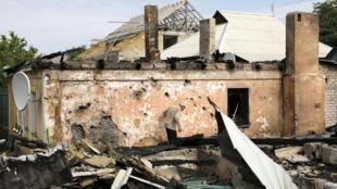 Un homme inspecte les dommages causés à sa maison par un bombardement, à Donetsk, le 17 août 2015.
