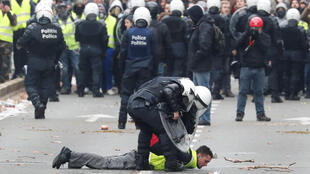 """A demonstrator is detained by police during the """"yellow vests"""" protest against higher fuel prices, in Brussels, Belgium, December 8, 2018."""