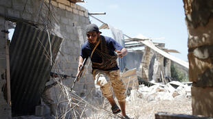 Un combatiente libio aliado del gobierno de unión nacional corre para protegerse durante un combate contra el grupo Estado Islámico en Sirte.