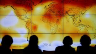 Participantes da Conferência Mundial sobre Mudanças Climáticas (COP21), em Paris, olham na tela um mapa múndi onde pode se ver as anomalias climáticas, em 8 de dezembro de 2015.