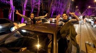 Iraníes celebran en Teherán el anuncio de la firma del acuerdo marco sbore el programa nuclear iraní.