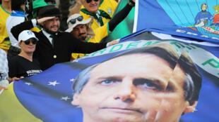 Des partisans du nouveau président brésilien brandissent un drapeau à son effigie, à Brasilia, le 1er janvier 2019.