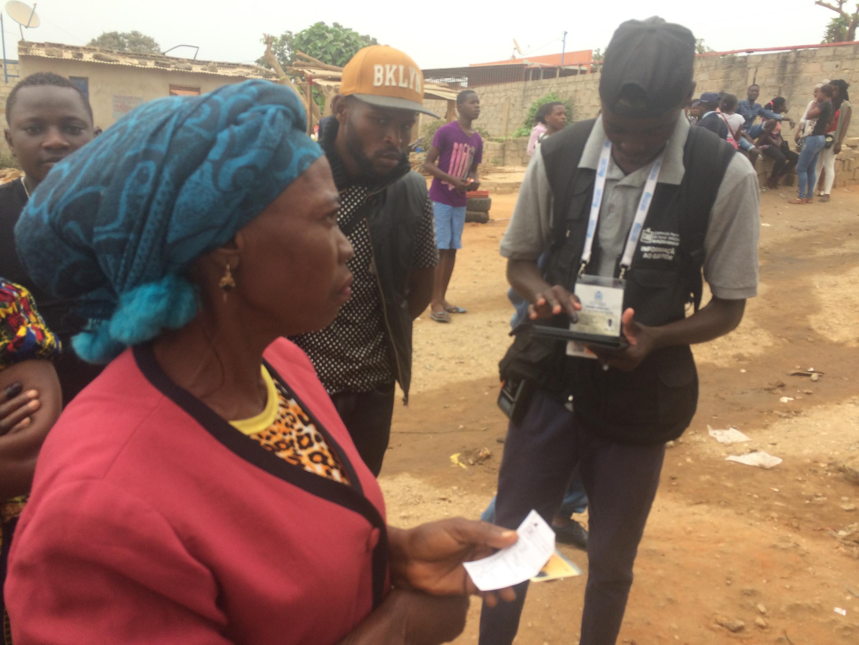 A l'extérieur d'un bureau de vote de Cimangola, à Luanda ce mercredi 23 août, une dame découvre qu'elle est convoquée dans un bureau plus éloigné.
