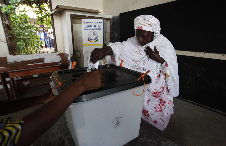 A woman votes in Sandravalia district at Federico de mayor school in Conakry, Guinea