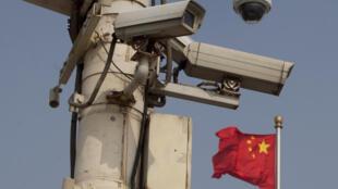 Le drapeau national chinois flotte derrière les caméras de sécurité sur la place Tiananmen le 4 juin 2012.