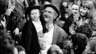 Achille Zavatta, à la fin de son numéro de clown, portant son fils Franck, en 1976.