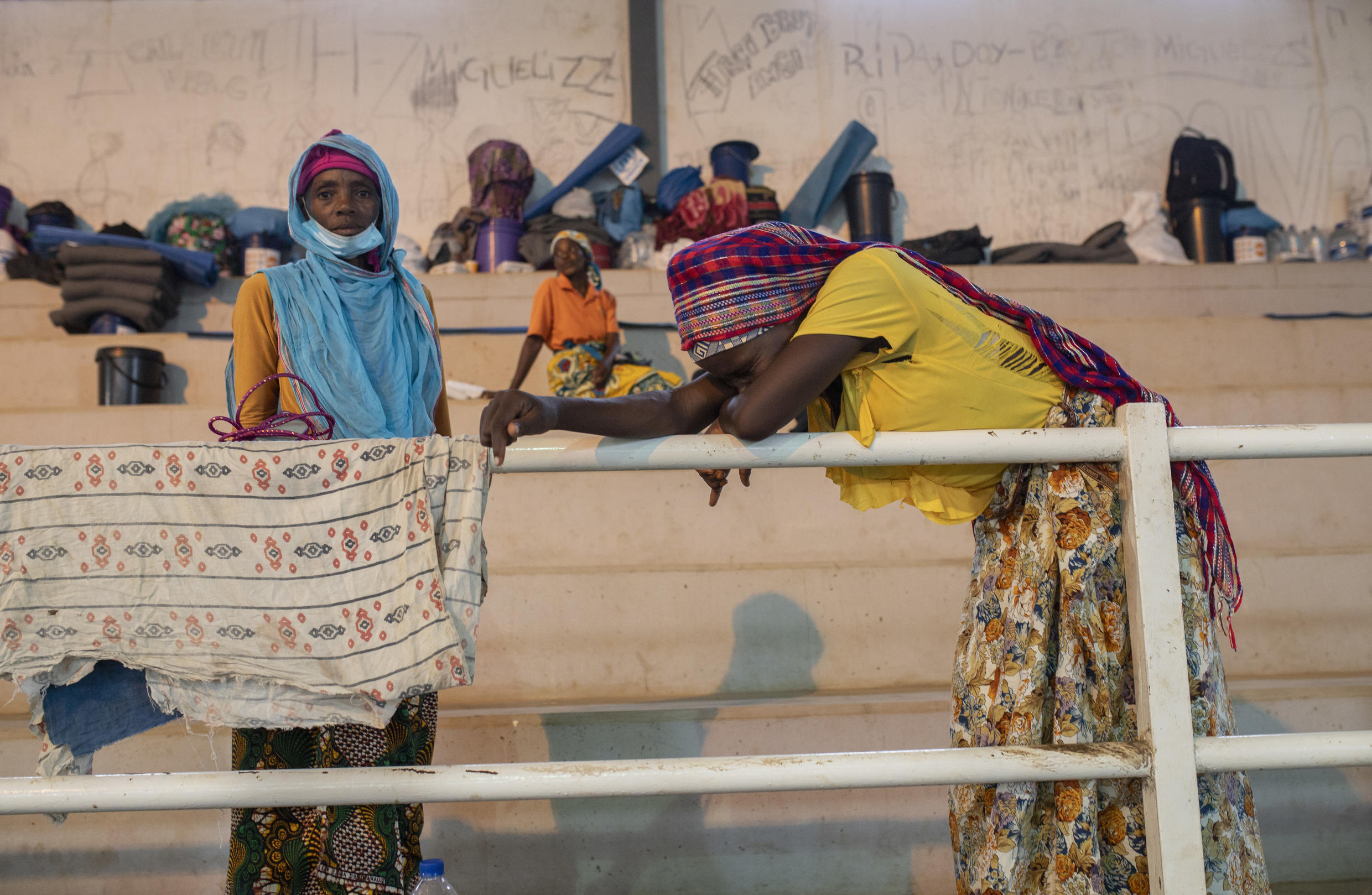 People who fled after the attack in Palma gather at a sports centre in Pemba