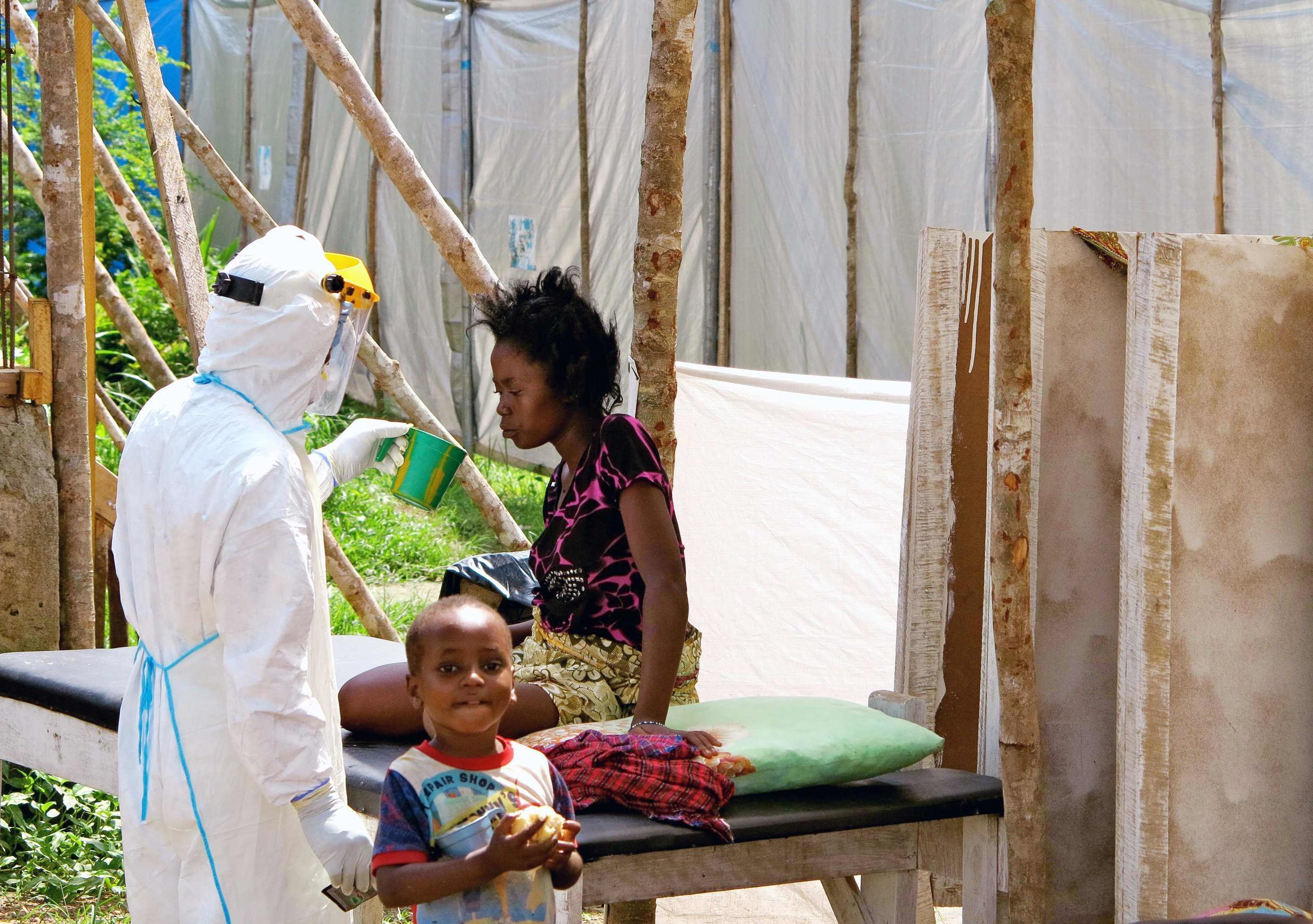 A health worker gives water to a female Ebola victim in a specialized treatment center in Kenema (Sierra Leone), July 2014.