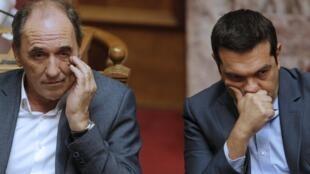 Primeiro-ministro grego (d), Alexis Tsipras, e ministro da Economia, George Stathakis, durante o debate parlamentar desta madrugada.