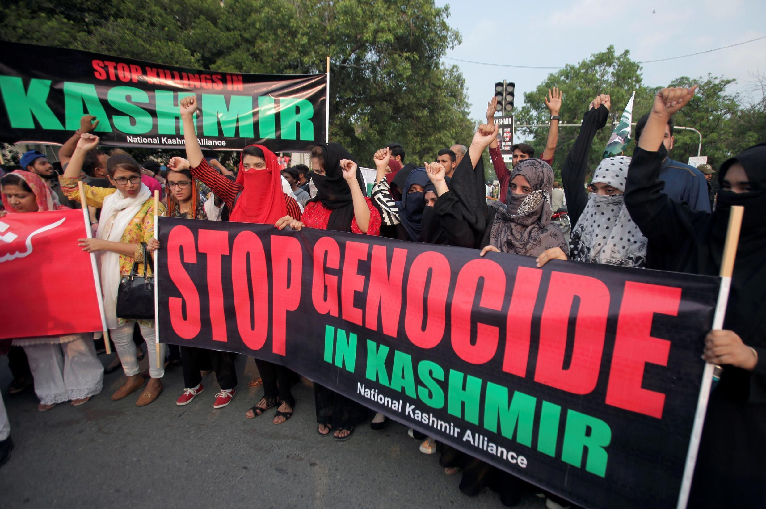 People hold banners and chant slogans during a rally in solidarity with the people of Kashmir, in Pakistan's city of Lahore.